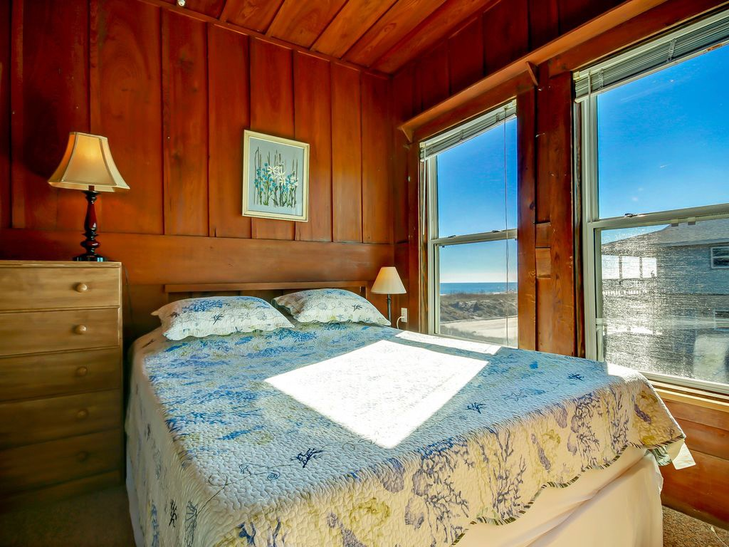 Queen bed with original knotty pine walls and peek a boo Oce