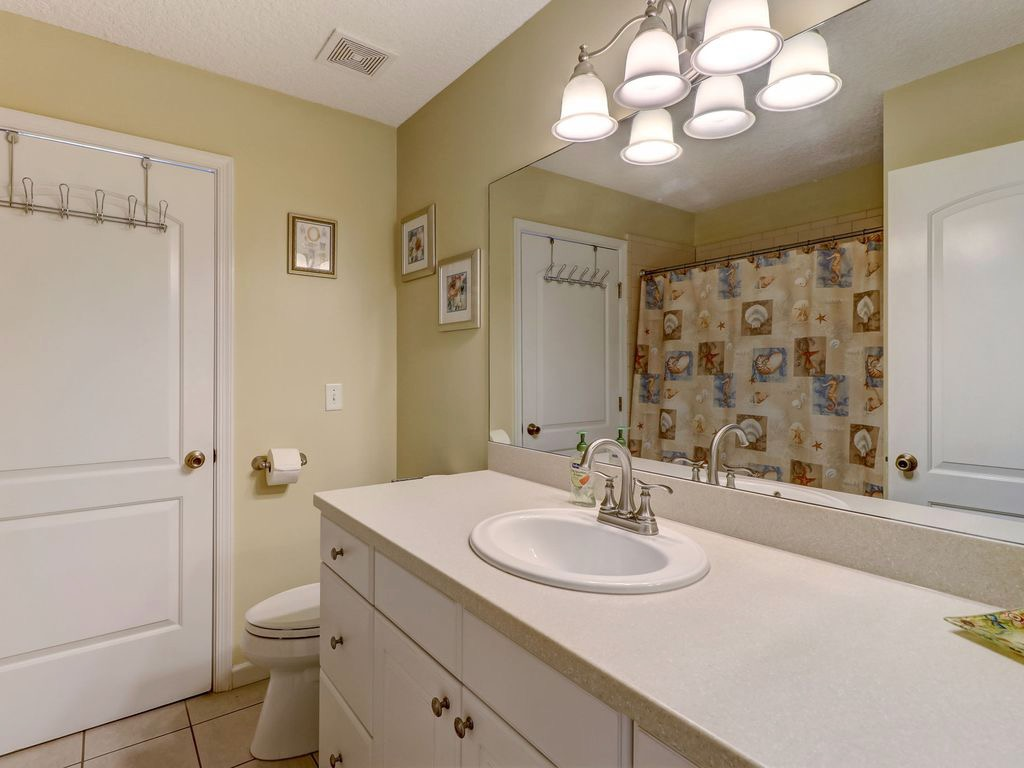 Hall bathroom with tub/shower combo and door leading to laun